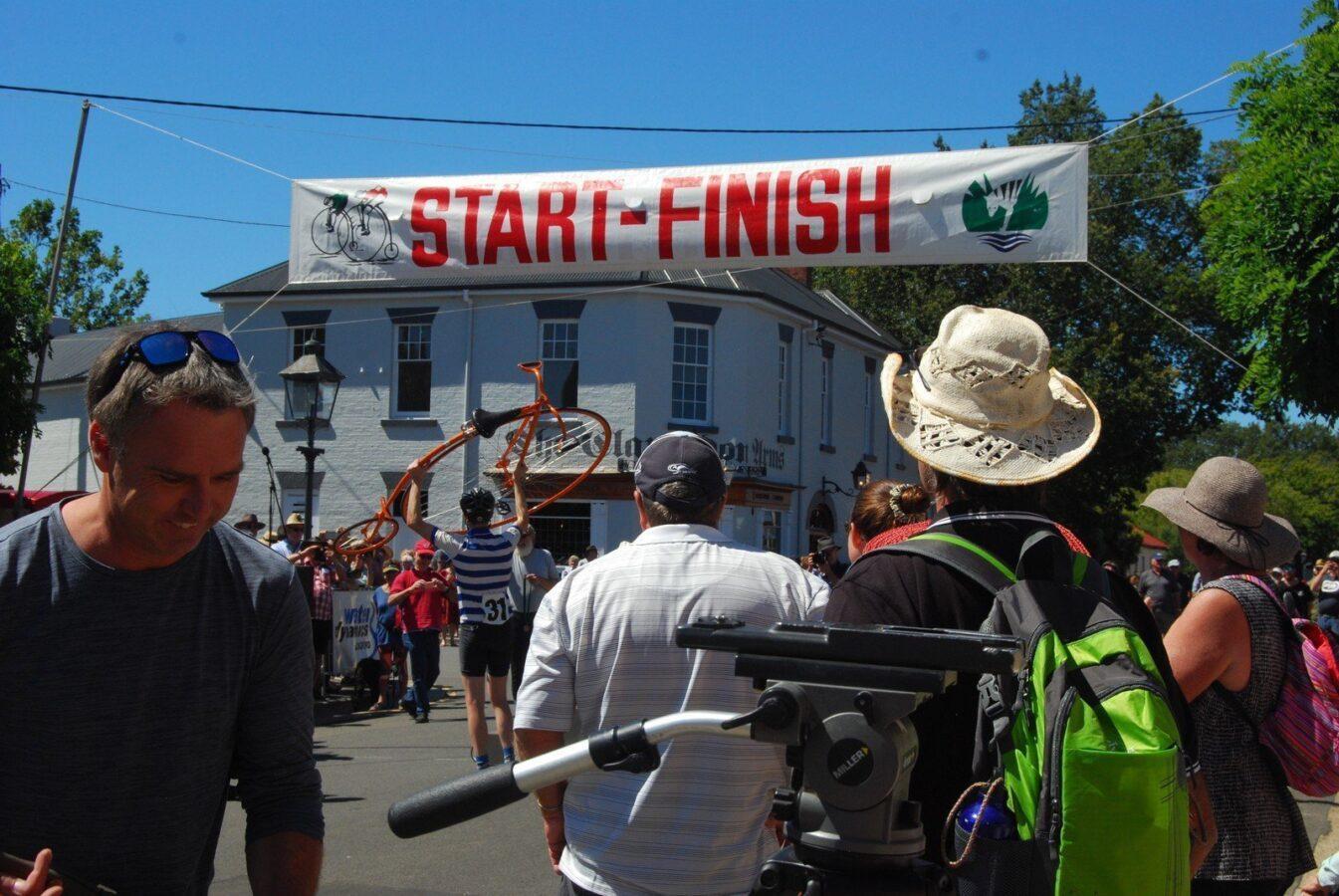 The Men's Winner holding his bike aloft